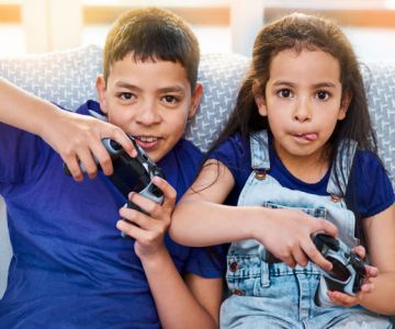 A kids sitting on sofa and playing video games
