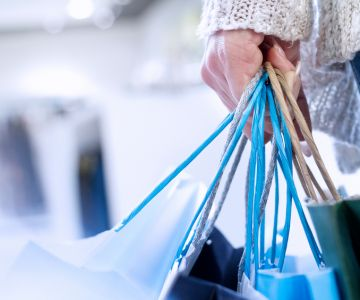 A person holding a shopping bags